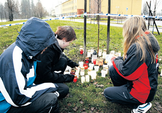 People light candles in front of the Jokela school centre in Tuusula where an 18-year-old killed six students, the head teacher and a nurse at his school before turning the gun on himself.