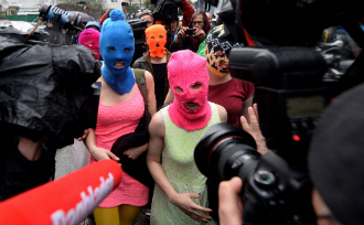 Wearing masks members of Russian punk group Pussy Riot, Nadezhda Tolokonnikova (L) and Maria Alyokhina (R) speak to journalists while leaving the police station of Adler, near Sochi.
