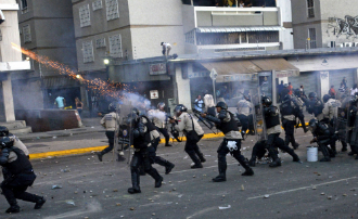 A riot policeman shoots tear gas during clashes with anti-government students holding a protest, in Caracas on 15 February.
