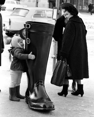 A little girl and a giant Nokia rubber boot in downtown Helsinki in February, 1966.