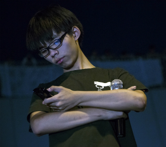 Joshua Wong, leader of the student group Scholarism, pauses on the stage to check a mobile device during a rally outside the Central Government Offices in Hong Kong.