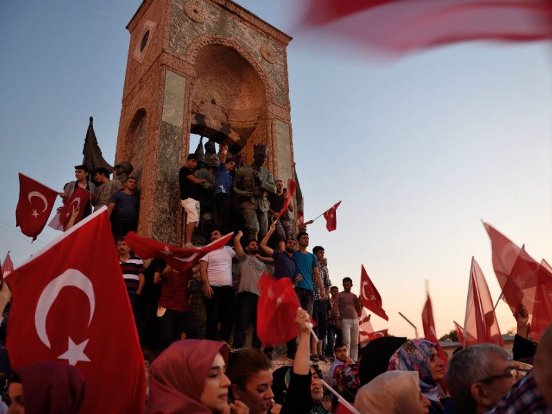 People waved flags around a statue of Mustafa Kemal Ataturk, the founder of modern Turkey, in Istanbul on 16 July, 2016, during a demonstration organised in support of President Recep Tayyip Erdoğan.