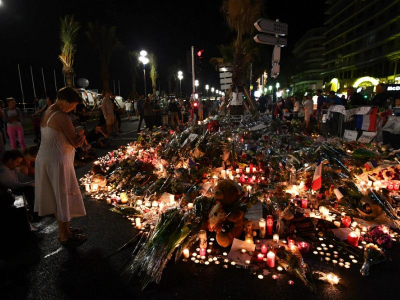 People gathered around a makeshift memorial for the victims of a deadly terror attack in Nice, France, on 17 July, 2016. The Islamic State has claimed responsibility for the attack that killed 84 people, according to a news service affiliated with the terrorist group.