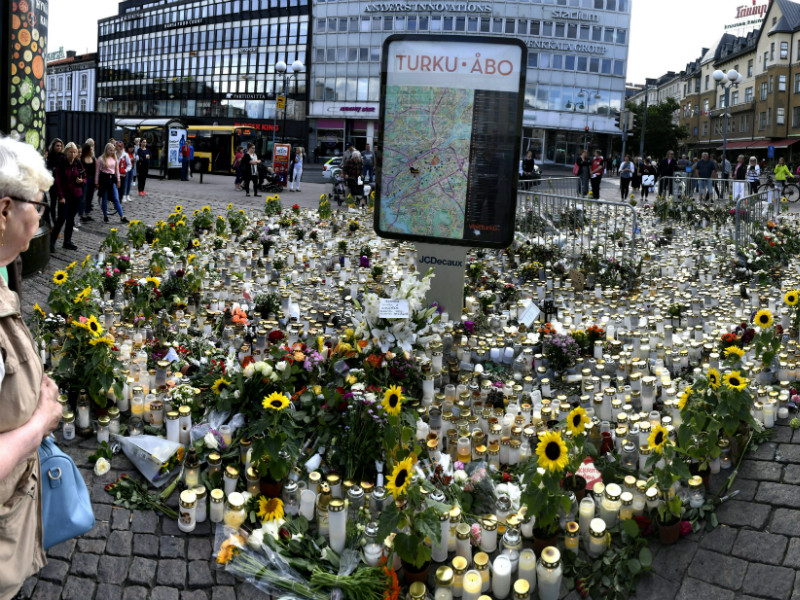 Passers-by stopped to look at a sea of candles and flowers at the Turku Market Square on Tuesday, 22 August, 2017.