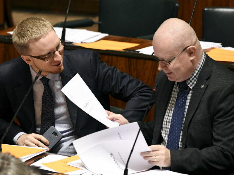 Simon Elo (left) and Jari Lindström of the Blue Reform talked during a plenary session in the Finnish Parliament on 19 December, 2017.