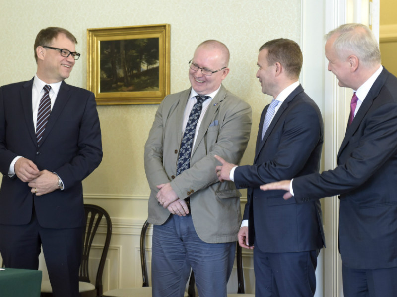 Prime Minister Juha Sipilä (Centre) and fellow cabinet members Jari Lindström (PS), Petteri Orpo (NCP) and Olli Rehn (Centre) were in high spirits before signing the so-called competitiveness pact, an agreement between the cabinet and labour market organisations to bring down unit labour costs, on 14 June, 2016.