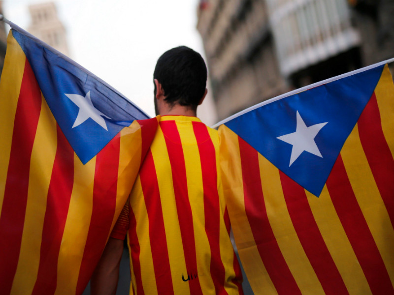 A man holding Catalan pro-independence flags in Barcelona during a general strike in called by Catalan unions on October 3, 2017. Independence movements in different parts of the world are believed to have gained momentum after the referendum in Catalonia, on 1 October.
