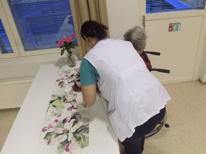 An employee assisted a customer with their breakfast in an elderly care facility in Pähkinärinne, Vantaa, on 23 October 2018. (Credit: Vesa Moilanen – Lehtikuva)