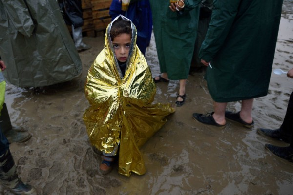 A child wrapped in a survival blanket looks as migrants queue for hot soup on March 13, 2016, in a makeshift camp at the border between Greece and Macedonia.