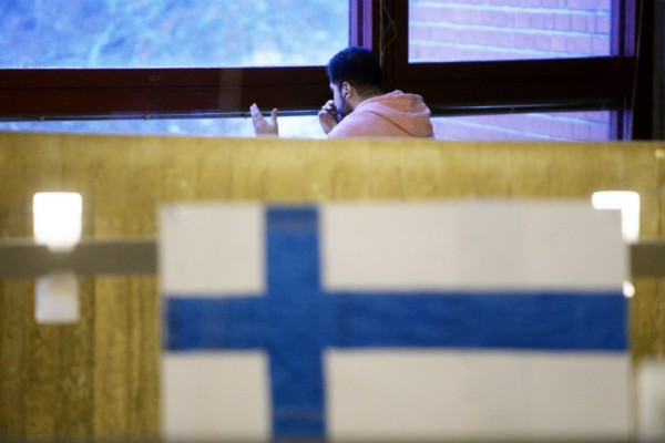 An asylum applicant gazed out of the window while speaking on the phone in a reception centre in Kirkkonummi on 2 February, 2016.