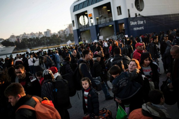 Refugees and migrants disembark a passenger ferry after arriving at the port of Piraeus in Athens on 31 January, 2016.