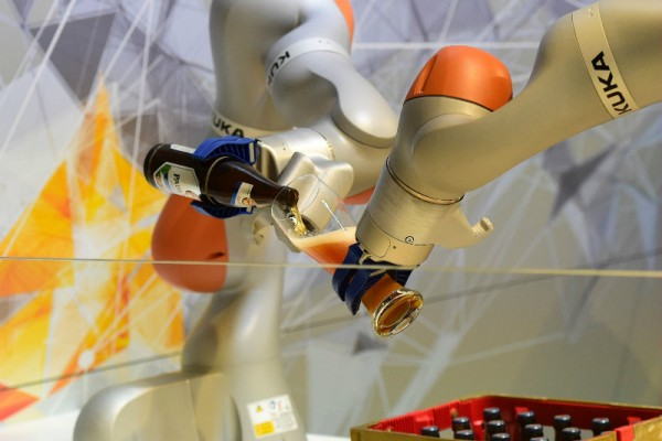 A file photo taken on 23 April, 2016, shows two robots filling a glass beer at the booth of KUKA, a German robotics manufacturer, on the eve the Hanover Fair in Germany.