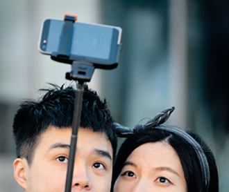 A couple use a 'selfie stick' to take a photo at a popular tourist spot in Seoul. In South Korea anyone selling an unregistered bluetooth-enabled selfie stick could face a fine or up to three years in prison, the Science Ministry announced last week.