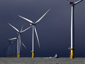 A boat passes between wind turbines at the London Array project. Birds, sharks and unexploded bombs from World War II are being blamed for holding up offshore wind farms in Europe.