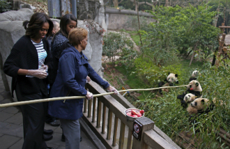 US First lady Michelle Obama (L) watches as her mother Marian Robinson (R) uses a pole to feed apples to giant pandas during their visit to Giant Panda Research Base in Chengdu.