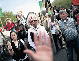 Members of the Cowboy and Indian Alliance, including Native Americans, farmers and ranchers from across the United States, march down Independence Avenue while demonstrating against the proposed Keystone XL pipeline on 22 April in Washington, DC.