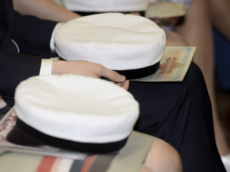 Student caps and matriculation examination certificates on the laps of graduates during a matriculation ceremony at the Normal Lyceum of Helsinki on 30 May, 2015.
