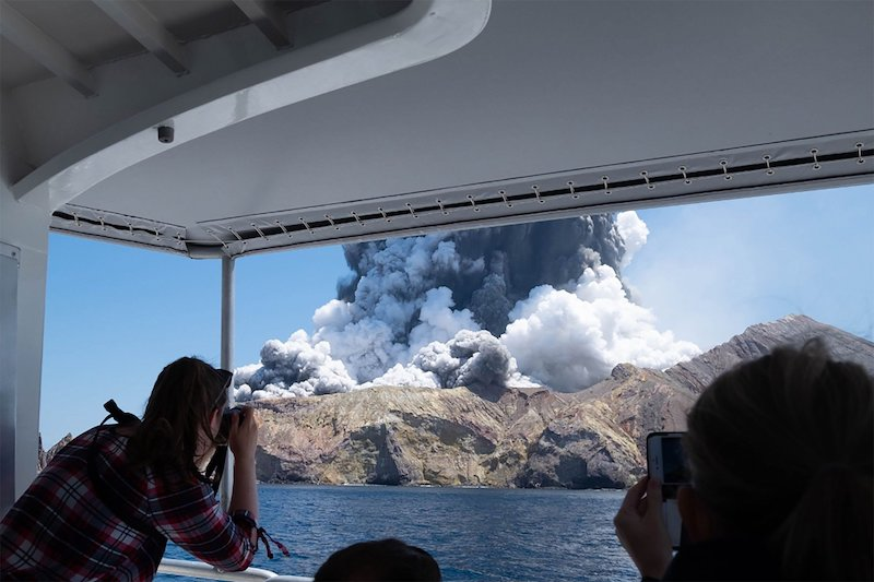 Onlookers watch as the White Island volcano erupts earlier today (Image: Lehtikuva)