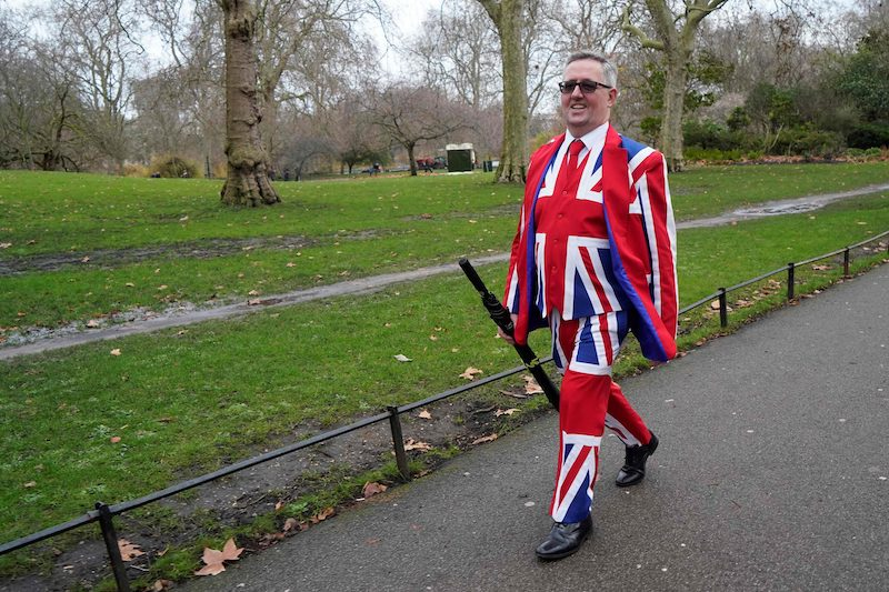 A man dressed in a Union Jack suit strolls through Hyde Park in London this morning.
