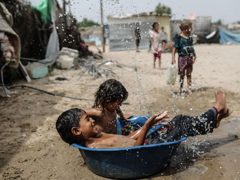 Palestinian children play with water in a slum on the outskirts of a refugee camp in the southern Gaza Strip on 17 July 2019. Estimates suggest that up to a billion people to leave their home region could be forced to leave their home region behind due to global warming. (Mahmud Hams – AFP/Lehtikuva)