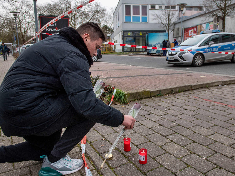 A man lays candles and flowers in front of one of the bars targeted in a shooting in Hanau, Germany, on 20 February 2020. (Thomas Lohnes – AFP/Lehtikuva)