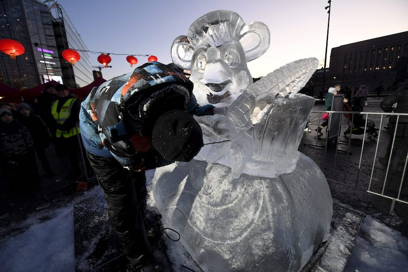 A man carves an ice sculpture of a rat to mark the beginning of the Year of the Rat.