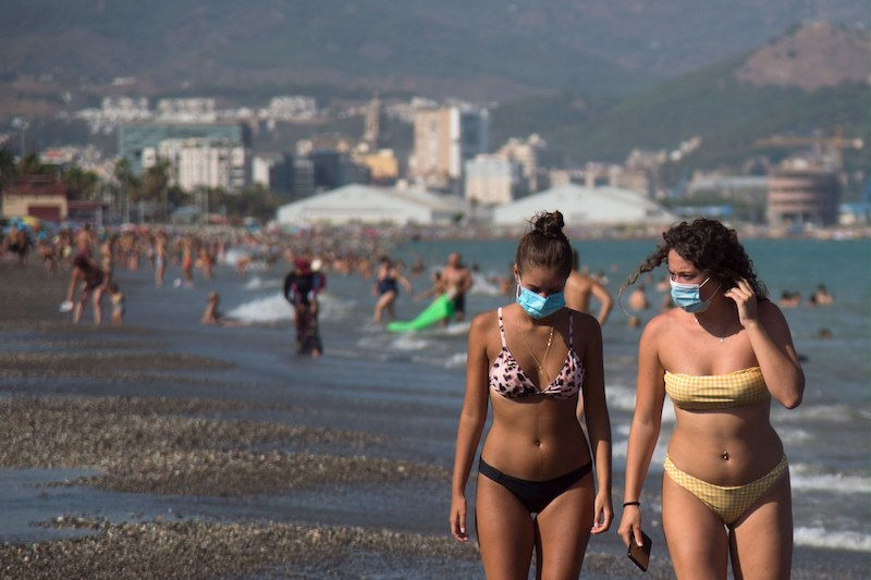 Holidaymakers don face marks on a beach in Malaga, Spain (Image: Lehtikuva)