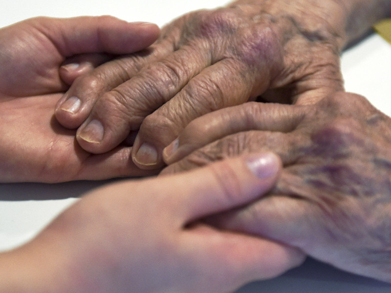 A nurse holding the hands of an elderly person in Helsinki on 9 August 2016. (Jussi Nukari – Lehtikuva)