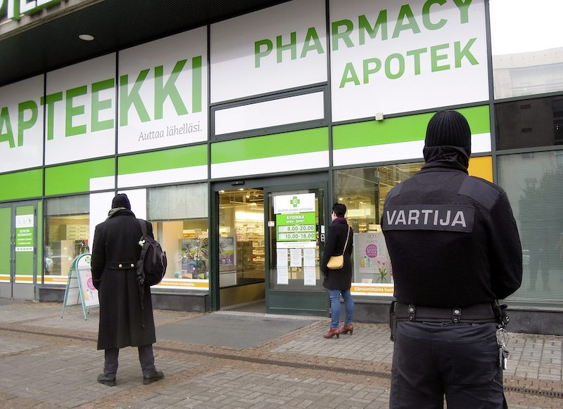 A security guard stands outside a pharmacy in Ruoholahti earlier today, which had instituted a 'one in, one out' policy for customers (Image: Lehtikuva)