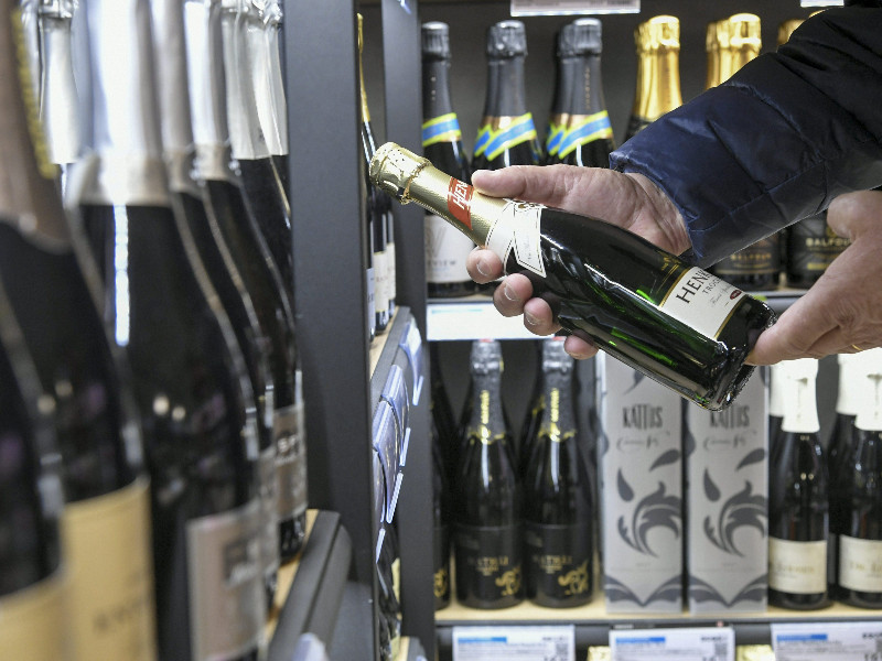 A man examined a bottle of sparkling wine in an Alko shop on 29 April 2020. (Markku Ulander – Lehtikuva)