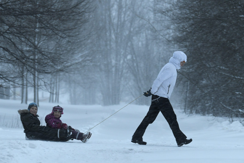 A mother drags her children through the snow with a sled
